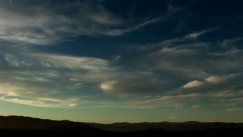Thin, wispy clouds drift across a blue green sky Stock Video Footage