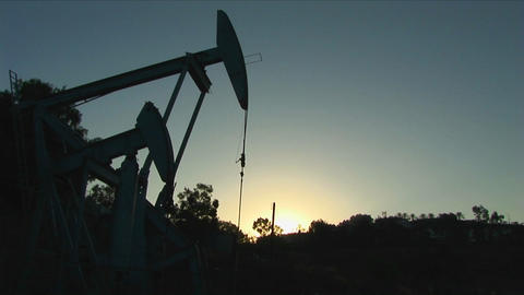 An oil well derrick is silhouetted against a glowing sky Stock Video Footage
