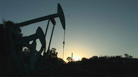 An oil well derrick is silhouetted against a glowing sky Footage