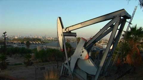 An oil well pumps oil with a sprawling suburban landscape behind Footage