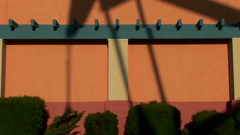 A giant oil rig casts a shadow against the side of a painted building Footage