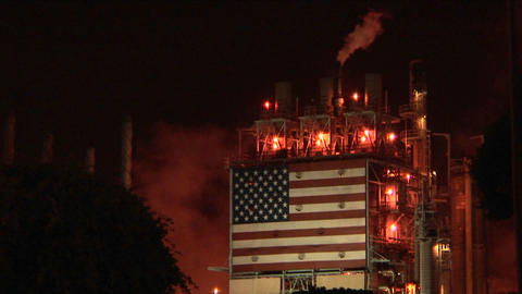 Smoke rises from an oil refinery, illuminated at night Stock Video Footage