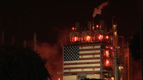 Smoke rises from an oil refinery, illuminated at night Footage