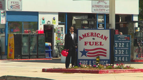 A man holding a gas can stands next to an American Fuel gas station with traffic zipping by Footage