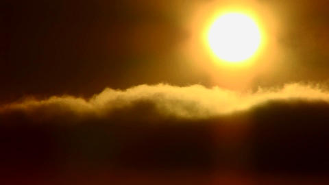 Time lapse of the sun behind golden clouds Stock Video Footage