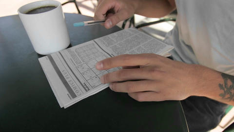 A person works on a newspaper puzzle while smoking and... Stock Video Footage