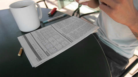 A person works on a newspaper puzzle while smoking and drink coffee Footage
