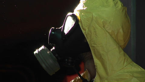 A man in a hazardous materials suit and gas mask turns to profile Footage