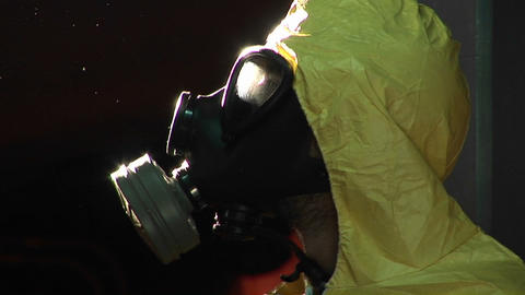 A man in a hazardous materials suit and gas mask turns to... Stock Video Footage