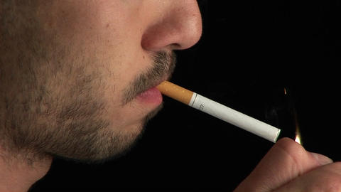 A man with a scruffy beard lights a cigarette in profile... Stock Video Footage