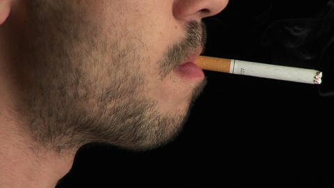 A man with a scruffy beard lights a cigarette in profile and smokes it Footage