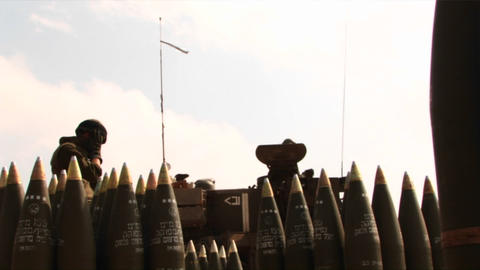 An army solider in Iraq stands amongst shells as a tank... Stock Video Footage
