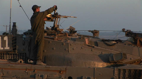 An Israeli soldier stands on a tank during a standoff at the Gaza strip Footage