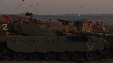 Israeli armored vehicles wait at an army staging post on the Gaza Strip border Footage