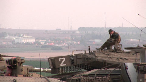 An Israeli army soldier sits atop a tank at the Gaza Strip border Footage