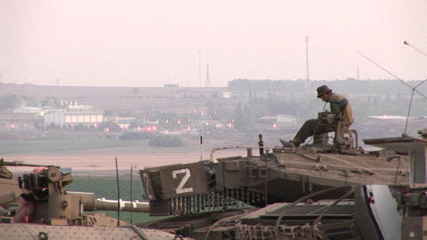 An Israeli army soldier sits atop a tank at the Gaza... Stock Video Footage