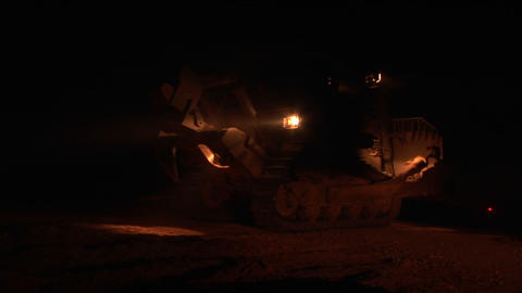 An Israeli armored bulldozer patrols the Israel - Gaza Strip border at night Footage