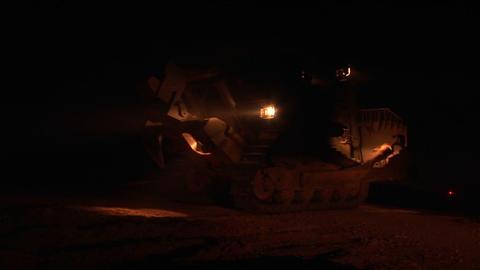 An Israeli armored bulldozer patrols the Israel - Gaza Strip border at night Footage