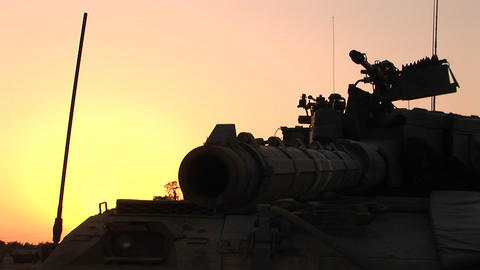 The barrel of an Israeli tank is silhouetted against an orange sky Footage