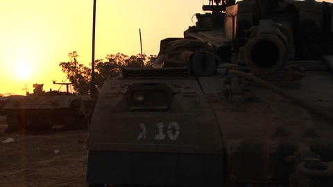An Israeli tank is silhouetted against a multi colored sky Footage