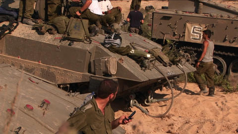 Israeli soldiers stand on top of their armored personnel carriers during a break in battle Footage