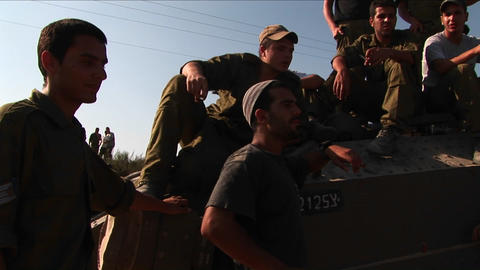 Off duty Israeli soldiers sit on a tank talk Stock Video Footage
