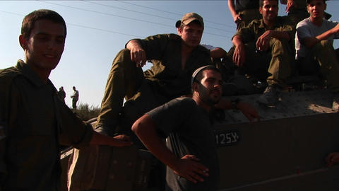 Off duty Israeli soldiers sit on a tank talk Stock Video Footage