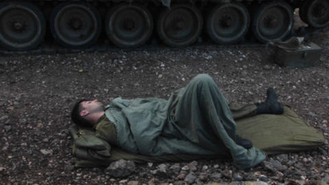 An Israeli army soldier sleeps on the ground, next to his... Stock Video Footage