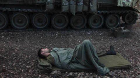 An Israeli army soldier sleeps on the ground, next to his tank, during the Israel - Lebanon war Footage