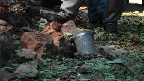 Israeli civilians look at the remains of a mortar shell in a forest Footage
