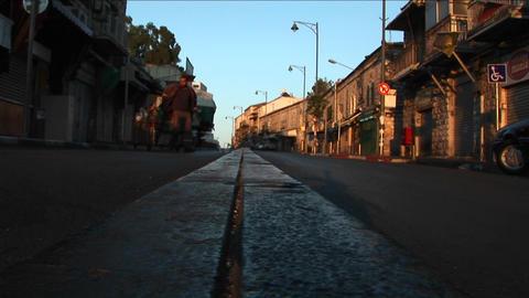 A garbage worker kicks a plastic bottle down a street in... Stock Video Footage