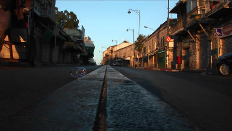 A garbage worker kicks a plastic bottle down a street in... Stock Video Footage