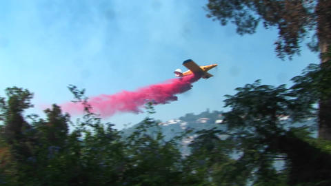 A firefighting plane dumps chemical retardant on a forest... Stock Video Footage