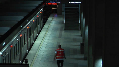 A woman enters the subway and a worker walks nearby Stock Video Footage