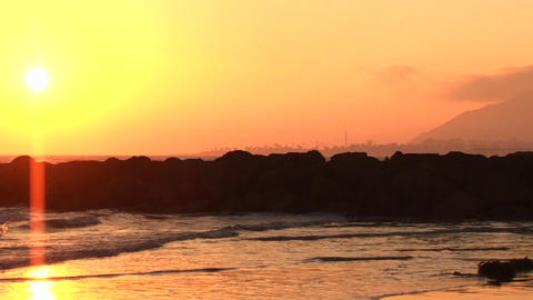 A surfer walks onto shore at sunset Stock Video Footage