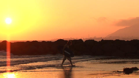 A surfer walks onto shore at sunset Footage
