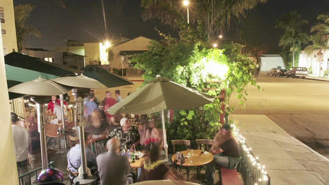 Time lapse of patrons outside a restaurant at night Stock Video Footage