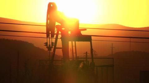 An oil derrick pumping at sunset Footage