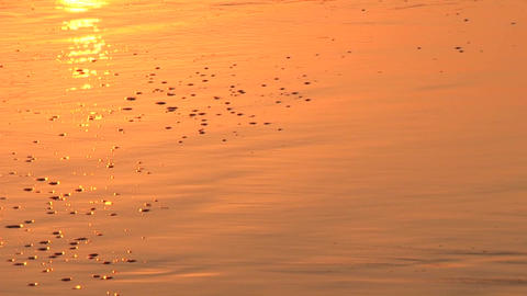Waves wash onto shore at sunset Stock Video Footage