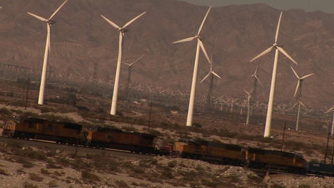 Dutch angle of many windmills rotating in a breeze as trains pass by Footage