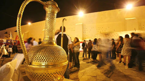 A time lapse of people walking pass a gold colored liquid container at night in Morocco Footage