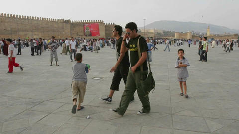 A time lapse of pedestrians walking near stone walls in Morocco Footage