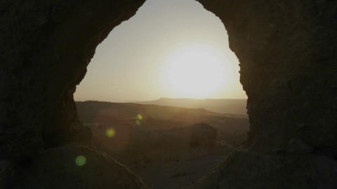 The sun is seen rising through a cave and above overlapping mountains Footage