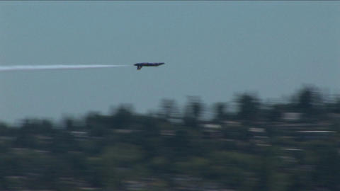 A Blue Angels jet barrel rolls and flies past other aircrafts Live Action