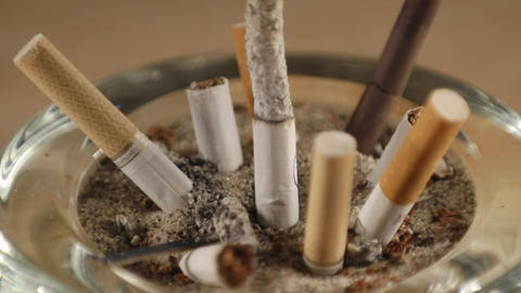 A time lapse of a cigarette burning among stubs in an ashtray Footage