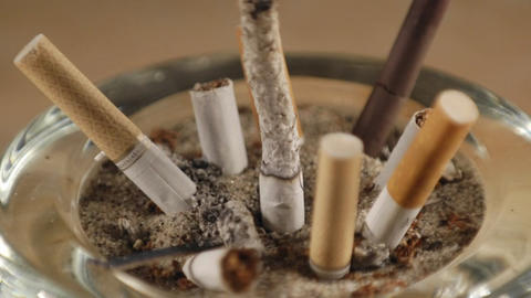 A time lapse of a cigarette burning among stubs in an... Stock Video Footage