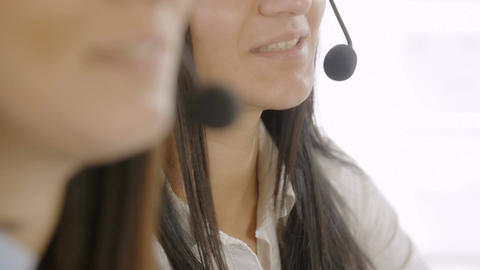 closeup footage on faces of call center operators: women at work with headset Footage
