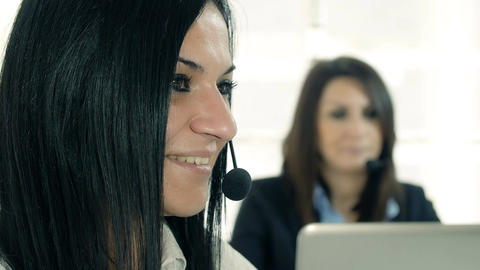closeup portrait of women working in a call center with headsets: customer care Footage