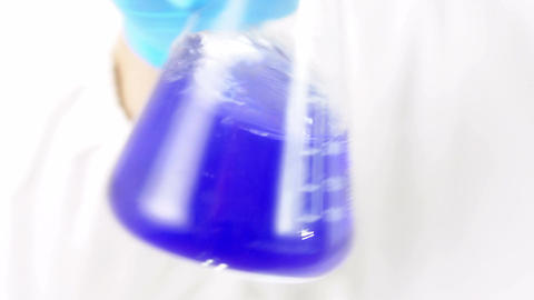 violet liquid in a glass beaker: scientist, research, biology Live Action