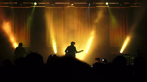 silhouette of a rock concert: musicians, guitarist, stage, audience Footage